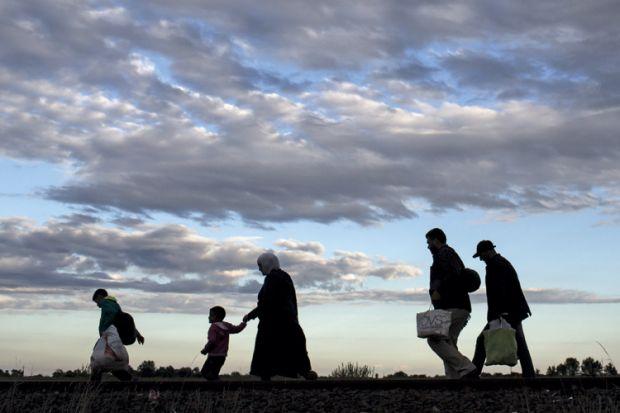 Migrants walk along rail tracks, Roszke, Hungary, 2015