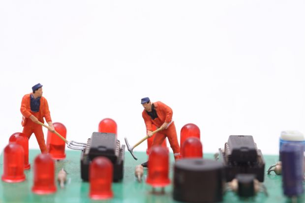 Miniature technicians repair a computer