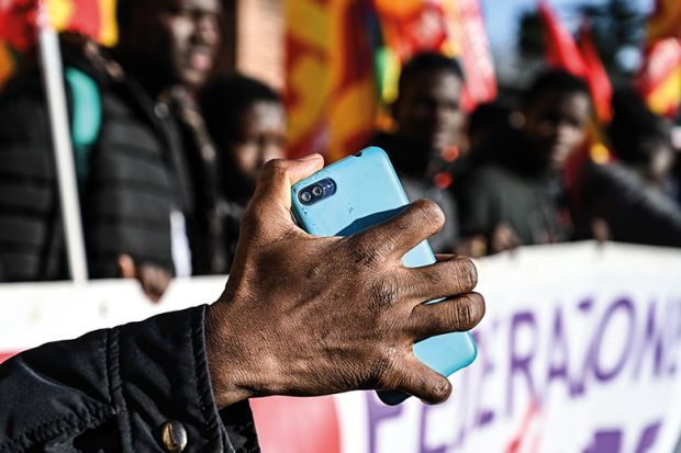 A migrant holds his mobile phone as members of anti-racism associations and migrants gather on Piazza della Repubblica in central Rome in December 2018 to protest the government's decree restricting the right to asylum
