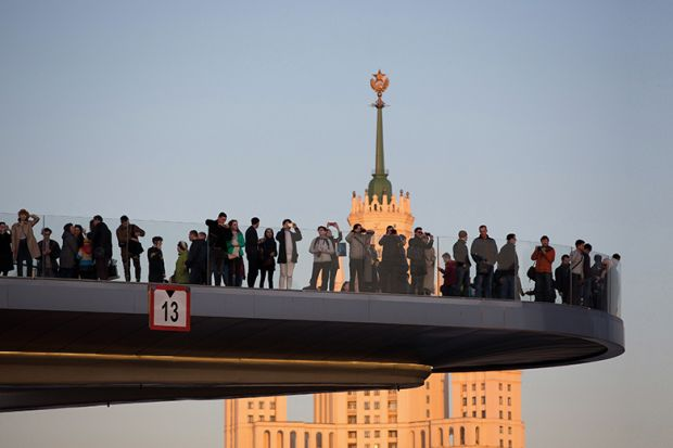 Visitors observe the city and one of the Seven Sisters skyscrapers from the 'floating bridge' in Zaryadye park in Moscow, Russia