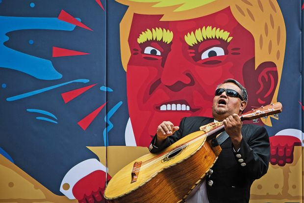 Man plays guitar in front of Donald Trump image