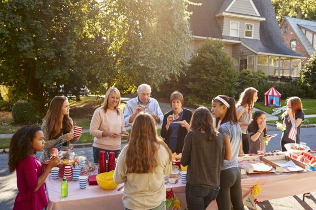 Neighbours talk and eat around a table at a block party representing collaboration between neighbouring universities