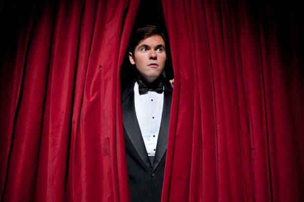 Nervous man peeking through stage curtains