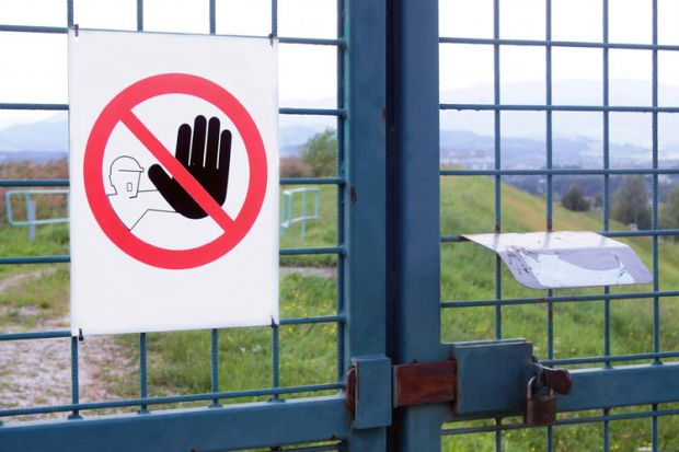 'No admission' sign on gated fence