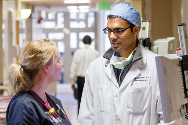 Nurse speaks with doctor. Stanford University Hospital and Clinics