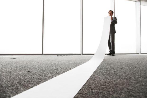 Office worker unrolling long sheet