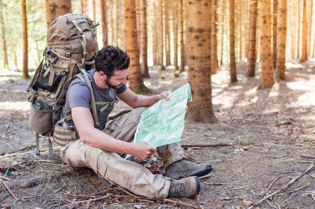 Outdoorsman/hiker sitting and reading map