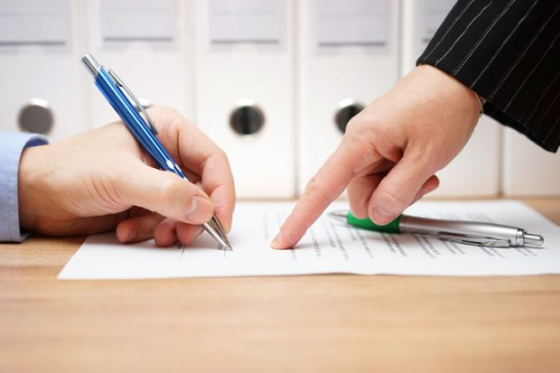 A person in a suit points to where to sign on a document