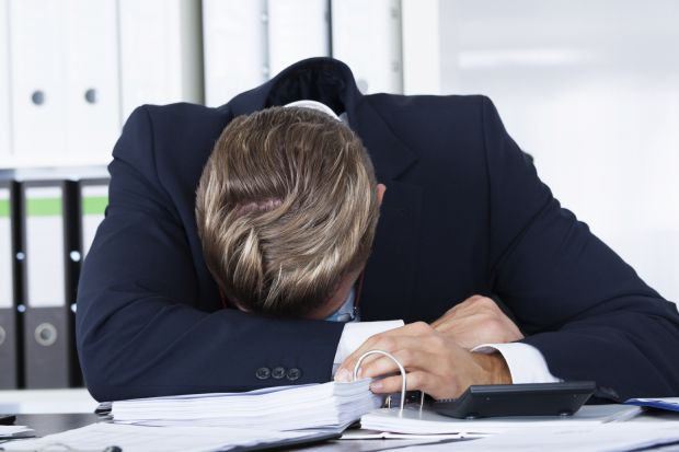 Overworked man slumped on desk