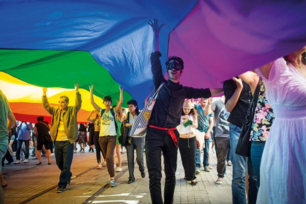 A protester in a mask holds up a Gay Pride flag during the annual Trans-sexual march on Istanbul's Istiklal Caddesi