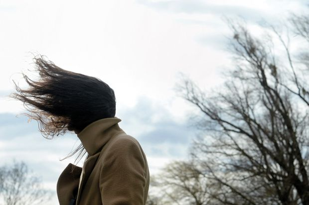 Woman with hair blown by wind