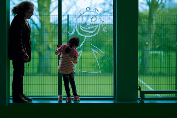 Child drawing in window