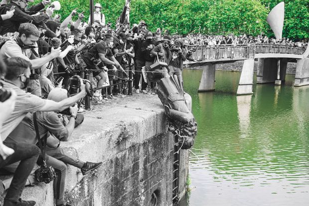 The statue of Edward Colston is pushed into the river Avon