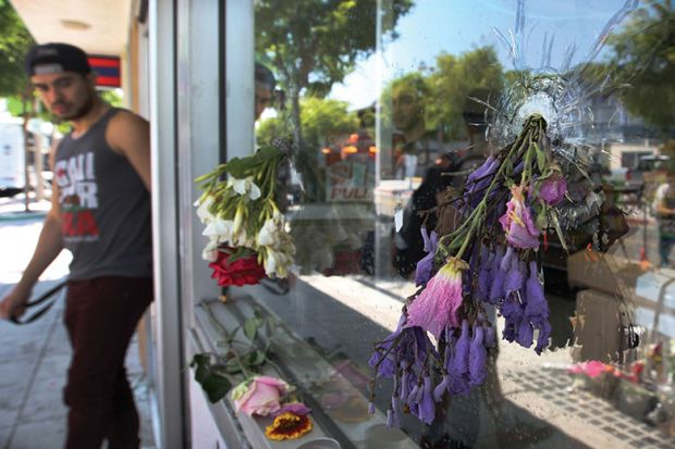 Flowers fill bullet holes in the windows of the IV Deli on May 25, 2014 in Isla Vista, California, after Elliot Rodger's murderous rampage