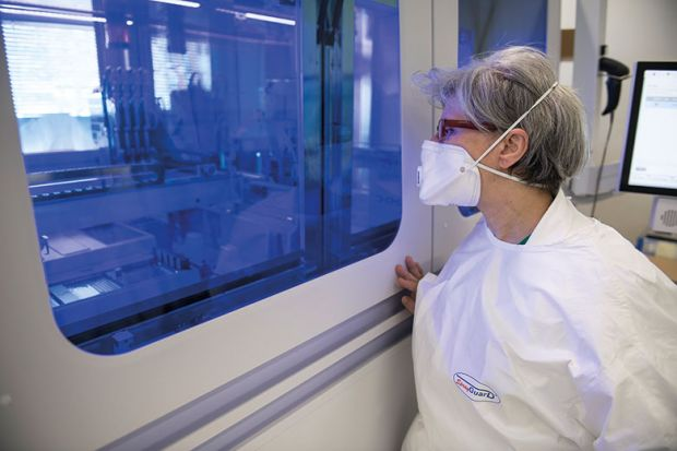 Healthcare workers work on the preparation of evaluation swabs for Coronavirus in research lab of Amedeo di Savoia hospital, Turin, Italy