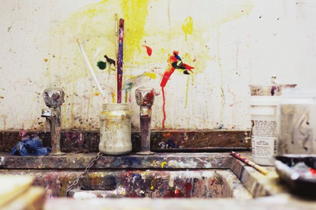 Paint and paintbrushes beside artist's kitchen sink