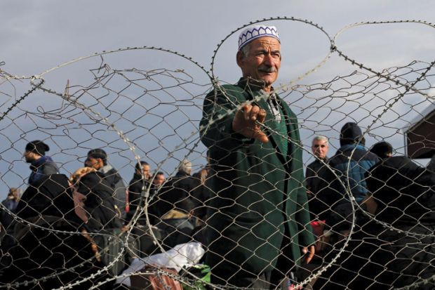 Palestinian man standing behind barbed fence, Gaza Strip, 2014