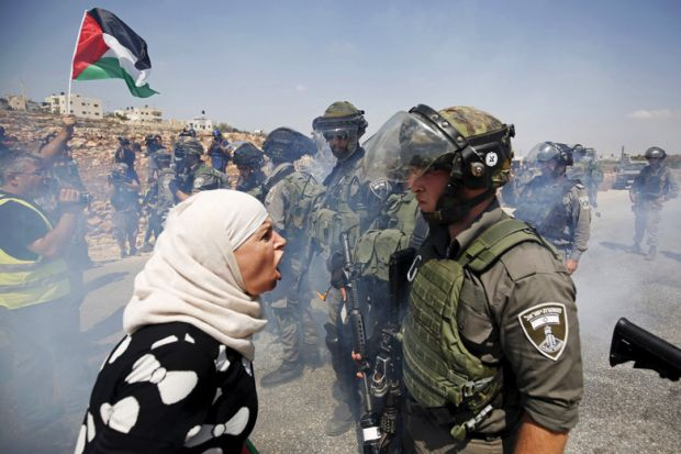 Palestinian woman argues with Israeli border policeman, West Bank