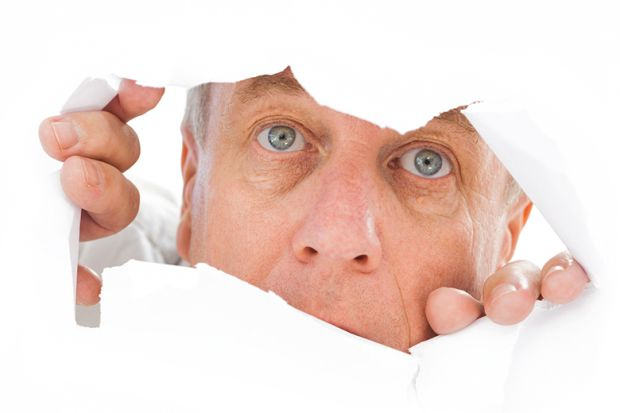 Man peeks through tear in paper