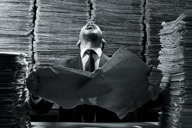 A man laughing amid a pile of paperwork