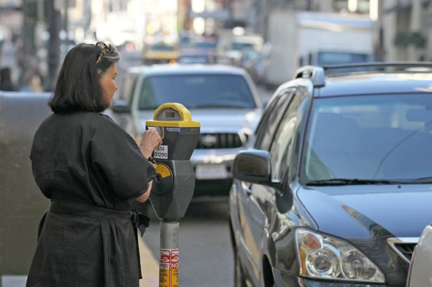 Woman pays a parking meter