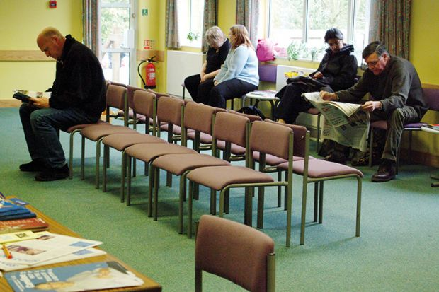 Patients sitting in doctors surgery waiting room