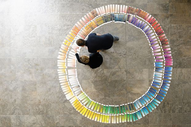People examining circle of paint swatches, viewed from above