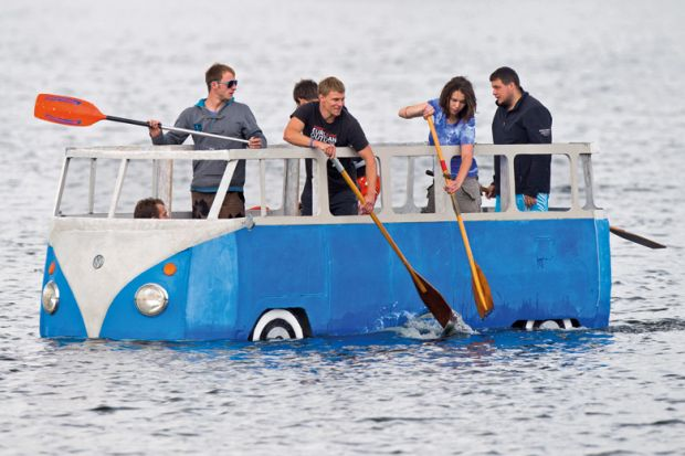 People paddling in floating Volkswagen camper van