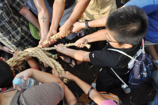 People pulling rope during tug of war festival