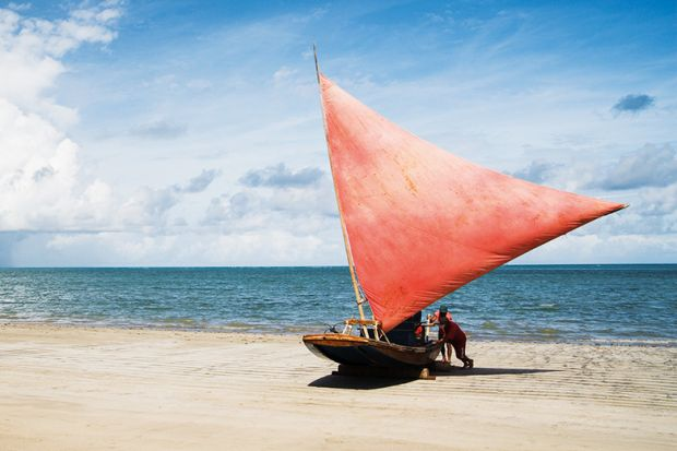 People pushing sailboat from sea onto beach