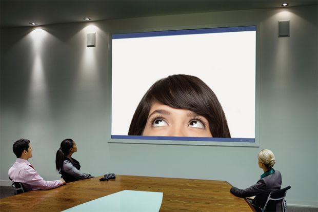 People taking part in Skype call in conference room