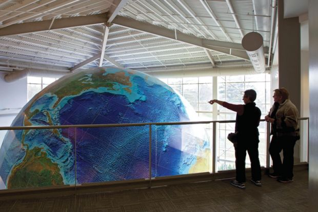 People viewing rotating globe, DeLorme Map Store, Yarmouth, Maine