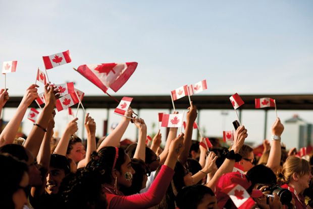 People waving Canadian flags