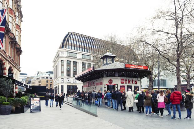 People queue for buying tickets from TKTS, the official London theatre ticket booth located at Leicester Square offering last minute and discount tickets for West End shows