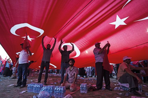 People underneath a Turkish flag