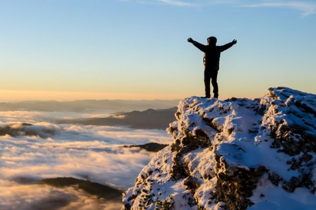 Person celebrating reaching top of mountain