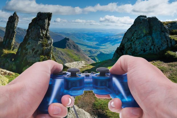 Person holding Sony PlayStation controller in hills