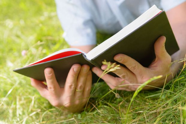 Person lying on grass reading book