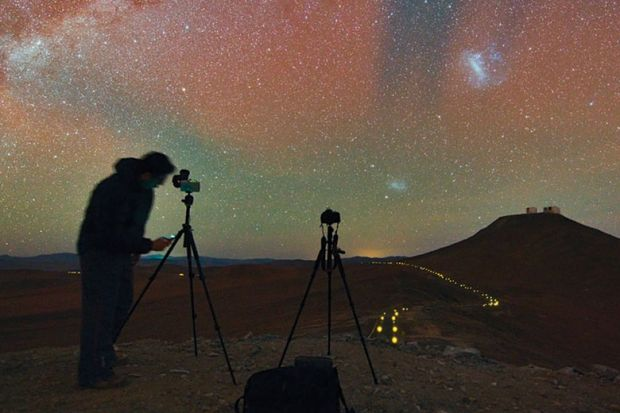 Person taking photographs of and recording night sky