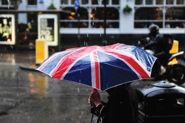 Person walking in rain carrying Union Jack umbrella