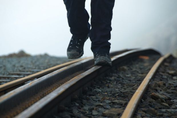Person walking on rail tracks (detail)