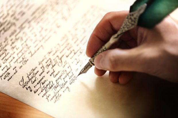 person writing letter with metal quill
