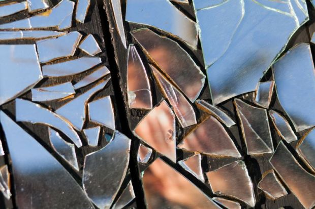 Person reflected in shattered mirror