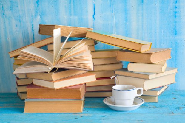 Piles of books with cup of tea