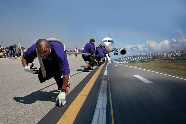 people pull plane along runway
