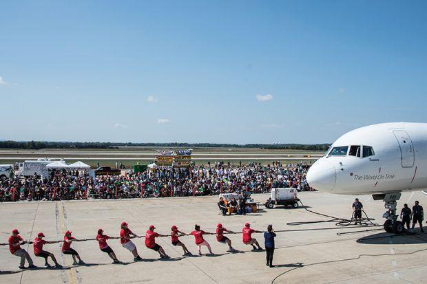 People pull plane on runway