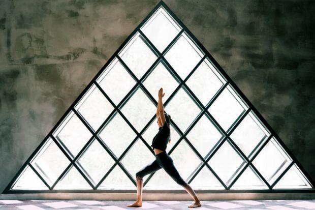 woman doing yoga by large triangular window