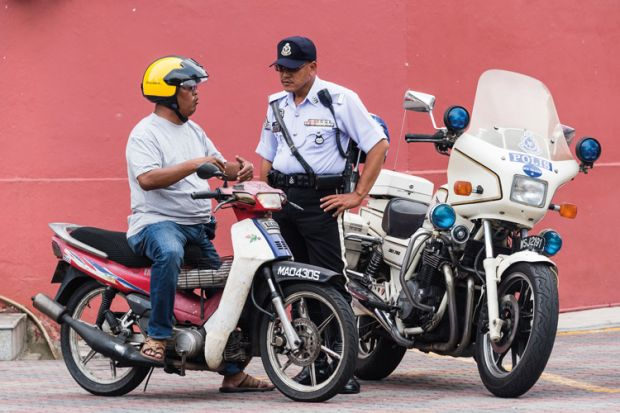 Policeman speaking to motorcyclist, Malacca, Malaysia