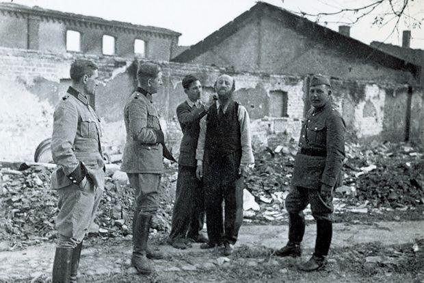 Polish civilian shaving Jewish man