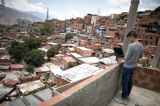 Boy with laptop on balcony